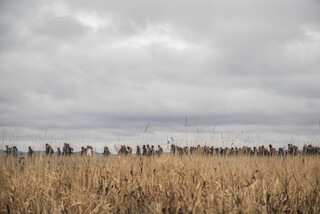 Women march from the Geo Dome in the Oceti Sakowin camp on Thanksgiving Day to show support after the initial wave of protectors gathered at the river.